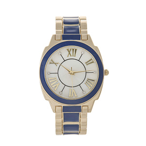 Gold tone cuff watch with Roman numerals, clear rhinestones and navy blue accents.