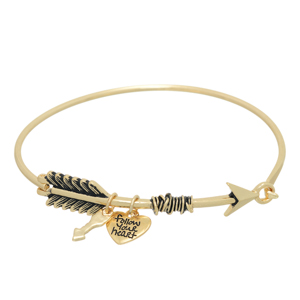 "Gold tone bangle latch bracelet featuring an arrow with a mini arrow charm and mini heart charm stamped ""follow your heart""."