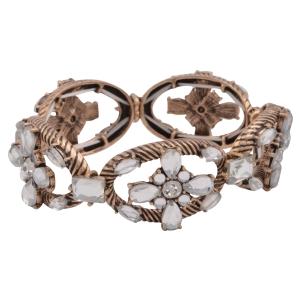 Burnished gold tone stretch bracelet featuring a clear rhinestone floral design.