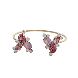 Gold tone cuff bracelet displaying pink and clear rhinestones at the opening.