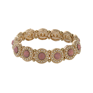 Gold tone stretch bracelet displaying disk with pink rhinestones surrounded by ivory beads.
