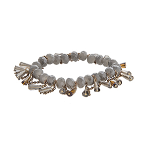 Gray stretch bracelet with dangling beads and gold tone chains.