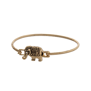 Burnished gold tone latch bangle bracelet displaying an elephant focal.