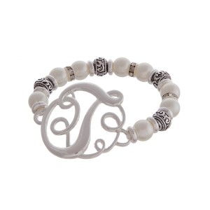 """Silver tone and pearl beaded stretch bracelet featuring the letter """"T"""" initial and accented with clear rhinestones."""