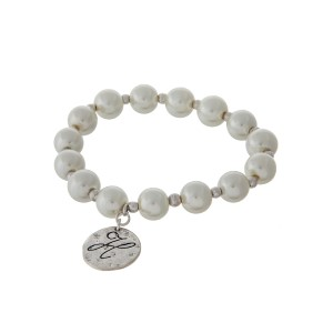 Gold tone stretch bracelet with cream pearl beads and a hammered disc stamped with a script 'H' initial.