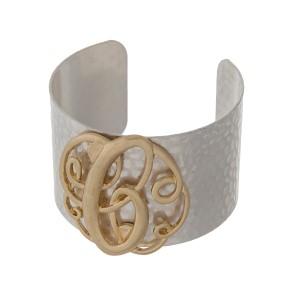 Hammered silver tone cuff bracelet with a gold tone script 'C' initial.