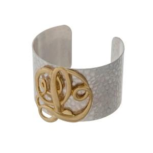 Hammered silver tone cuff bracelet with a gold tone script 'L' initial.