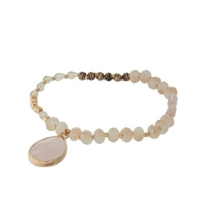 Ivory and champagne beaded stretch bracelet with a teardrop charm.