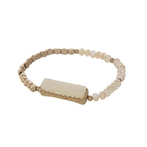 Gold tone stretch bracelet featuring an ivory faux druzy stone and champagne beads.