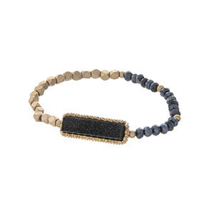 Gold tone stretch bracelet featuring a black faux druzy stone and hematite beads.