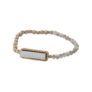 Gold tone stretch bracelet featuring a silver faux druzy stone and gray beads.