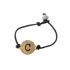 Brown cord bracelet with a gold 'C' stamped disc and a freshwater pearl bead closure.