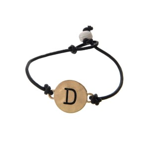 Brown cord bracelet with a gold 'D' stamped disc and a freshwater pearl bead closure.