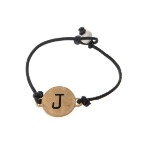 Brown cord bracelet with a gold 'J' stamped disc and a freshwater pearl bead closure.