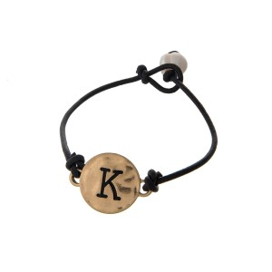 Brown cord bracelet with a gold 'K' stamped disc and a freshwater pearl bead closure.