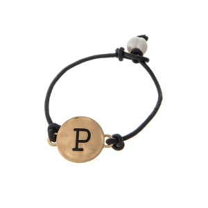 Brown cord bracelet with a gold 'P' stamped disc and a freshwater pearl bead closure.