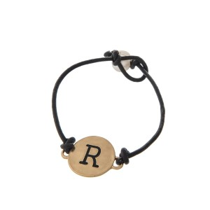 Brown cord bracelet with a gold 'R' stamped disc and a freshwater pearl bead closure.