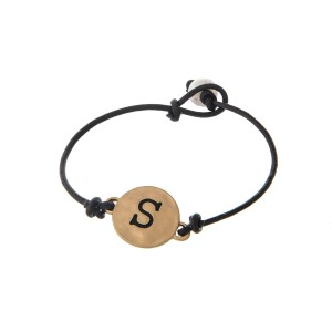 Brown cord bracelet with a gold 'S' stamped disc and a freshwater pearl bead closure.