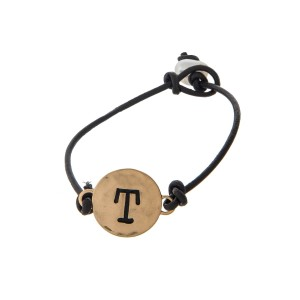 Brown cord bracelet with a gold 'T' stamped disc and a freshwater pearl bead closure.