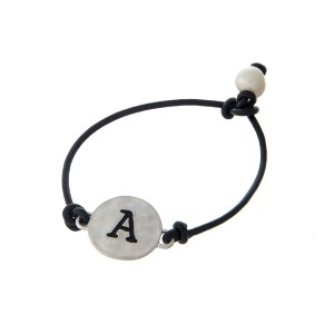 Black cord bracelet with a silver 'A' stamped disc and a freshwater pearl bead closure.