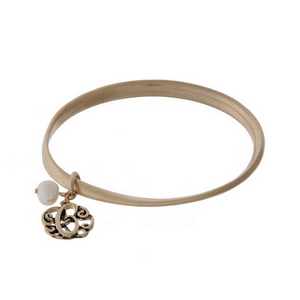Burnished gold tone twist bangle with a script 'C' initial and freshwater pearl charms.