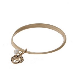 Burnished gold tone twist bangle with a script 'E' initial and freshwater pearl charms.