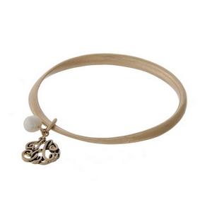 Burnished gold tone twist bangle with a script 'H' initial and freshwater pearl charms.