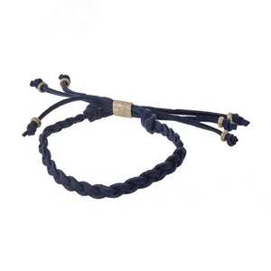 Navy blue, braided faux suede adjustable bracelet with gold tone accents.