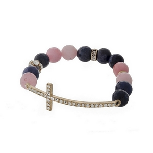 Navy blue and pink beaded stretch bracelet with a hammered gold tone cross focal.