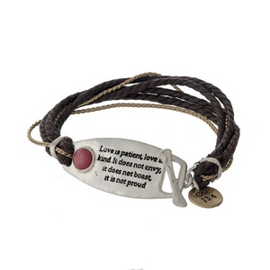 "Brown cord bracelet with a silver tone bar stamped with ""Love is patient, love is kind. It does not envy, it does not boast, it is not proud"" and a toggle closure."