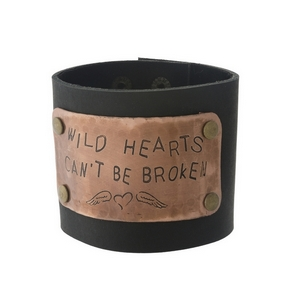 "Black faux leather cuff with a hammered plaque, stamped with ""Wild hearts can't be broken."" Approximately 2.5"" in width."