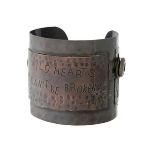 "Hammered copper cuff bracelet with a plate stamped "" Wild hearts can't be broken."" Approximately 2.5"" in width."