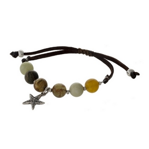 Brown faux leather cord, adjustable bracelet with neutral colored beads and a silver tone starfish charm.