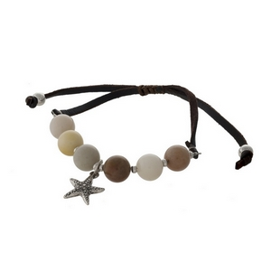 Brown faux leather cord, adjustable bracelet with peach colored beads and a silver tone starfish charm.