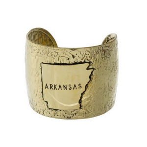 "Hammered gold tone cuff bracelet displaying the state of Arkansas. Approximately 2"" in width"