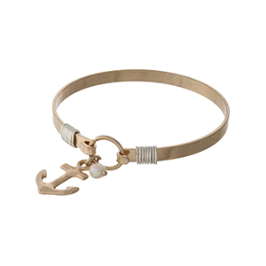 Gold tone bangle bracelet with an anchor charm.
