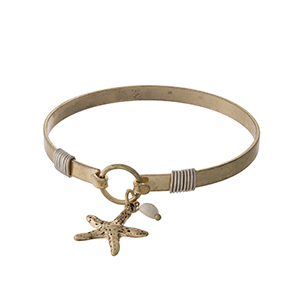 Gold tone bangle bracelet with a starfish charm.