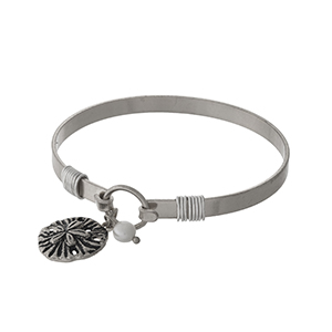 Silver tone bangle bracelet with a sand dollar charm.