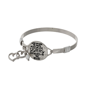 "Silver tone bangle bracelet stamped with ""Side by side or miles apart, we are Sisters, connected by the heart"" and accented with a small heart charm."
