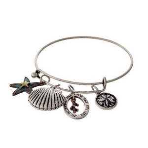 """Silver tone adjustable bracelet with a stamped charm saying """"Dreaming of the sea and sun"""" and sea shell charms."""