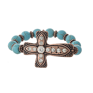 Turquoise stretch bracelet with a copper tone cross, accented with clear rhinestones.