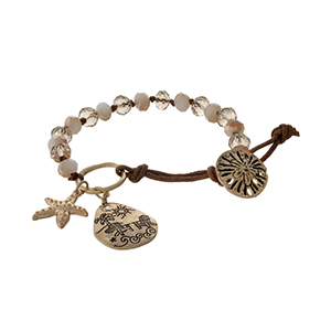 Brown cord bracelet with ivory and champagne beads, a stamped beach scene charm, and a sand dollar closure.