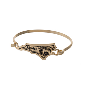 Gold tone bangle bracelet with the city map of Raleigh, North Carolina stamped on the state shape.