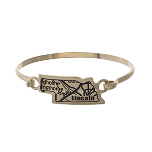 Gold tone bangle bracelet with the city map of Lincoln, Nebraska stamped on the state shape.