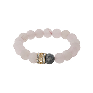 Rose quartz beaded stretch bracelet with a gold tone bead accent.