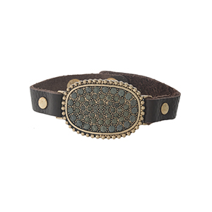 Brown leather snap bracelet with a gold tone focal, accented with gray rhinestones.