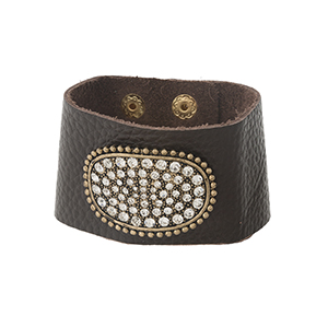 Brown leather snap bracelet with a gold tone and clear rhinestone pave focal.