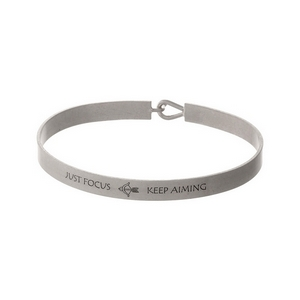 """Silver tone, brass bangle bracelet stamped with """"Just Focus, Keep Aiming."""""""