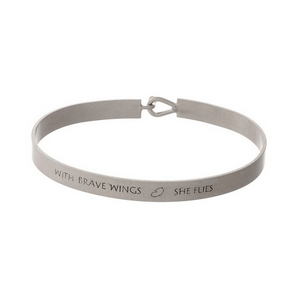"""Silver tone, brass bangle bracelet stamped with """"With Brave Wings, She Flies."""""""