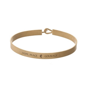 """Gold tone, brass bangle bracelet stamped with """"Hope Peace Courage."""""""